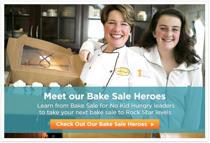 Mom and daughter pose with box of professional chocolate cupcakes with white frosting - Meet our Bake Sale Heroes. Learn from Bake Sale for No Kid Hungry leaders to take your next bake sale to Rock Star levels - Check Out Our Bake Sale Heroes button